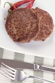 fresh juicy beef meat hamburger with dry pepper on white plate over tablecloth with cutlery high resolution hidef