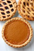 High angle closeup of three fresh baked holiday pies. The traditional American desserts - Pumpkin, Cherry and Apple pie are Thanksgiving staples. Vertical format.