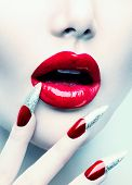 Makeup and Manicure. Red Long Nails and Red Glossy Lips. Sensual Mouth. Nail Art. Beautiful Sexy Lips. Fashion Model Woman Face. Professional Make-up. Perfect Skin
