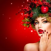 Christmas Winter Woman. Beautiful New Year and Christmas Tree Holiday Hairstyle, Make up, manicure. Beauty Fashion Model Girl over holiday red Background. Creative Hair style decorated with Baubles