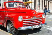 HAVANA,CUBA - NOVEMBER 6,2014 : Beautiful and shiny vintage red Ford car parked next to a hotel