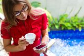 Woman reading Mails on smartphone while drinking coffee on balcony in tropical setting