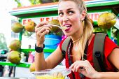 European Woman eating at mobile kitchen stall on Jakarta travel exploring Indonesia street food