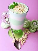 Mint milk dessert in glass, peanuts and mint jelly candies on color background