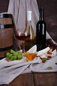Supper consisting of Camembert and Brie cheese, honey, wine and grapes on napkin and wine barrel on curtain background