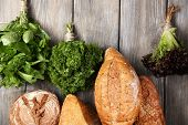 Fresh baked bread and fresh herbs, on wooden background