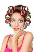 Beautiful girl in hair curlers isolated on white