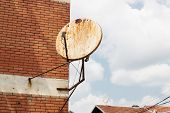 rusty satellite dish on the outside wall