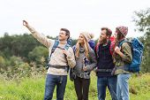 adventure, travel, tourism, hike and people concept - group of smiling friends with backpacks taking selfie