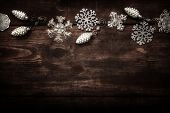 Silver snowflake Christmas ornament border on a wooden background