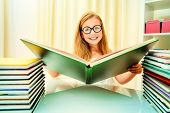 Teen girl sitting at table at home with piles of books and smiles. Educational concept.