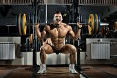 pic of lifting weight  - very brawny guy bodybuilder execute exercise squatting with weight in gym - JPG