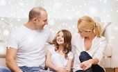 family, childhood, happiness and home concept - smiling parents and little girl sitting on floor at home