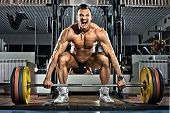 picture of snatch  - very brawny guy bodybuilder execute exercise deadlift with weight in gym - JPG