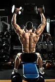 picture of execution  - very brawny guy bodybuilder execute exercise with dumbbells on deltoid muscle shoulder - JPG