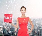 sale, christmas, holidays and people concept - smiling woman in red dress with sale sign over snowy city background