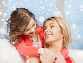 people, motherhood, family, winter and adoption concept - happy mother and daughter hugging at home
