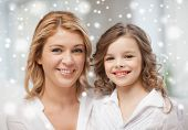 people, motherhood, family, winter and adoption concept - happy mother and daughter