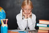 Tired school girl sitting on desk in classroom