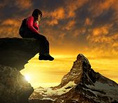 Girl sitting on a rock, in the background mount Matterhorn at sunset Swiss Alps, Europe