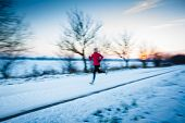 Winter running - Young woman running outdoors on a cold winter day (motion blurred image, color toned image)