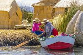 PUNO, PERU, MAY 5, 2014: Uros islands on Titicaca lake -  Local women in traditional attire work on fishing boat