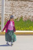 PUNO, PERU, MAY 5, 2014: Woman in traditional attire walks down the street