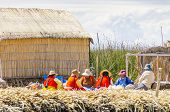 PUNO, PERU, MAY 5, 2014: Inhabitants of Uros islands on Titicaca lake gather together for some rest and meal