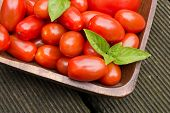 Tomatoes With Basil In A Wooden Bowl On Floorboards