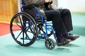 Disabled senior man using a wheelchair in a hospital ward