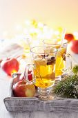 glass of mulled apple cider with orange and spices, christmas decoration