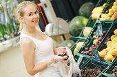 Shopping. Woman choosing bio food fruit cherry in vegetable store or supermarket