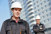 Team of smiling foreman builders workers in protective uniform at construction building site
