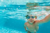 Small boy swimming wearing goggles under water