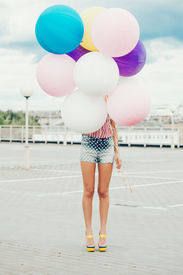 picture of latex woman  - Happy young woman standing behind big colorful latex balloons - JPG