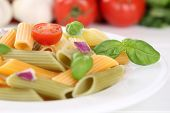image of noodles  - Colorful Penne Rigate noodles pasta food meal with tomatoes and basil on plate - JPG