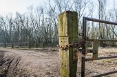 stock photo of gate  - Part of a crooked old gate mounted on an oak railway sleeper - JPG