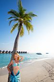 Young beautiful girl stands near by palm tree on background of ocean Maldives