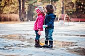 image of country girl  - toddler boy and girl kisses on the walk in spring puddle with paper boats in hands - JPG