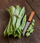 picture of phaseolus  - Piattoni green beans with knife on the old wooden table - JPG