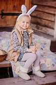 picture of country girl  - happy child girl wearing bunny ears for easter sitting on stairs with patchwork blanket at country house - JPG