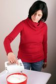 stock photo of whip-hand  - Portrait of a woman preparing whipped cream - JPG