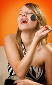 image of face-powder  - Nice looking girl applying face powder with closed eyes - JPG
