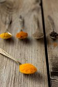 picture of curcuma  - Curcuma powder on old metal spoon wooden table - JPG