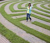 Young Woman Walking Through a Maze with Her Cellphone