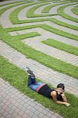 Young Woman Talking on the Phone in a Grass Maze