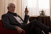 foto of opulence  - Horizontal view of senior millionaire smoking cigar - JPG