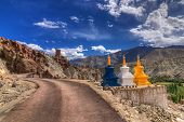 stock photo of jammu kashmir  - Three colourful buddhist religious stupas at Leh Ladakh Jammu and Kashmir India religious landscape himalayasmountain road blue sky scenery scenic chorten cloudshigh road travel three - JPG