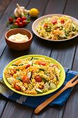 picture of sweet-corn  - Two plates of vegetarian pasta salad made of tricolor fusilli sweet corn cucumber and cherry tomato with mayonnaise in the back photographed with natural light  - JPG