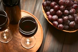 stock photo of wine grapes  - Glasses of red wine with red globe grapes and a bottle of wine photographed on dark wood with natural light  - JPG